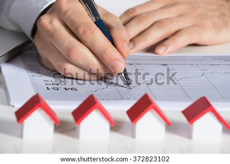 Cropped image of businessman preparing financial chart with house models at office desk - stock photo
