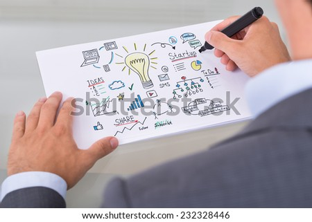 Cropped image of businessman preparing startup plan on paper at table in office - stock photo