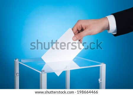 Cropped image of businessman putting paper in election box against blue background - stock photo