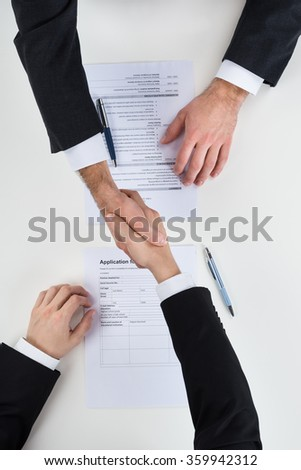 Cropped image of businessman shaking hands with male candidate at desk - stock photo