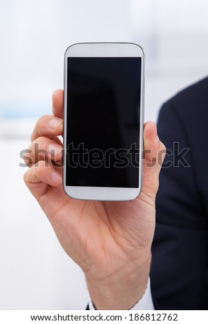 Cropped image of businessman showing smartphone in office - stock photo