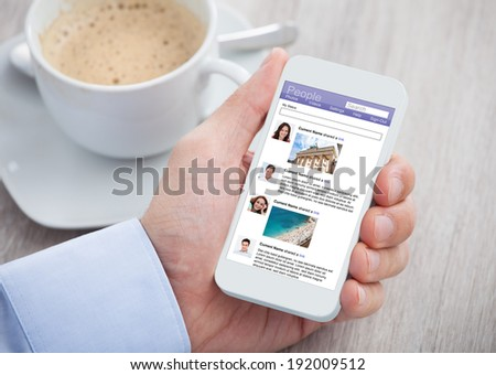 Cropped image of businessman surfing social networking site on mobilephone at office desk - stock photo
