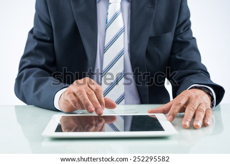 Cropped image of businessman using digital tablet