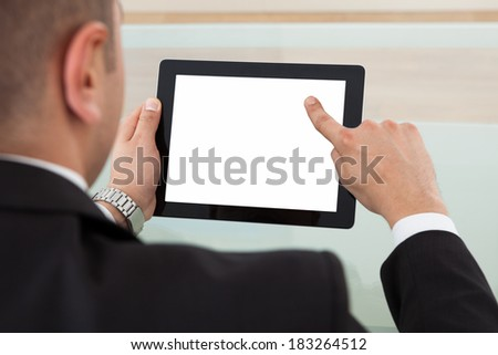 Cropped image of businessman using digital tablet in office - stock photo