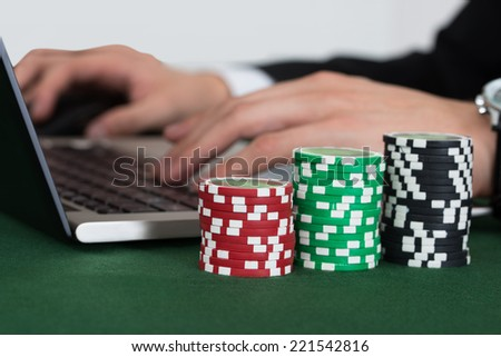 Cropped image of businessman using laptop by stacked casino chips at desk in office - stock photo