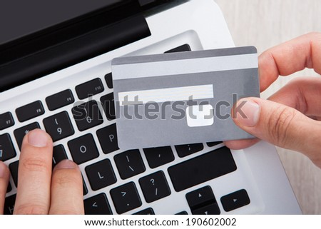 Cropped image of businessman with credit card shopping online at desk in office - stock photo