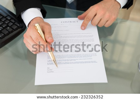 Cropped image of businessman with pen and contract document at desk in office