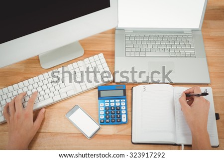 Cropped image of businessman writing on diary while using computer at desk in office - stock photo