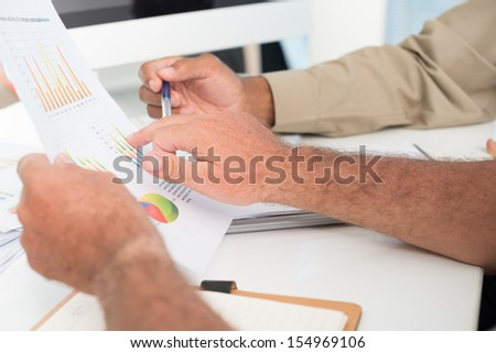 Cropped image of businesspeople making a strategy analysis on the foreground - stock photo
