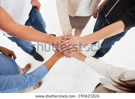 Cropped image of businesspeople stacking hands in office - stock photo