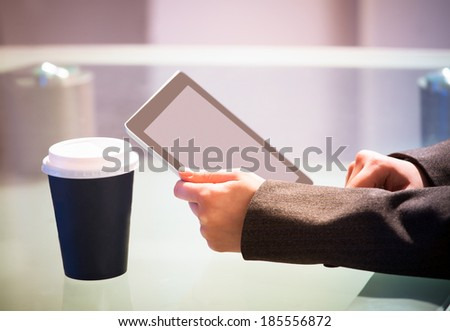 Cropped image of businesswoman holding digital tablet with disposable cup on desk - stock photo