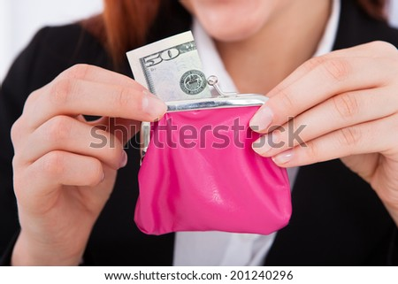 Cropped image of businesswoman putting 50 dollar bill in small purse - stock photo