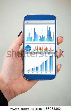 Cropped image of businesswoman's analyzing charts on smartphone in office