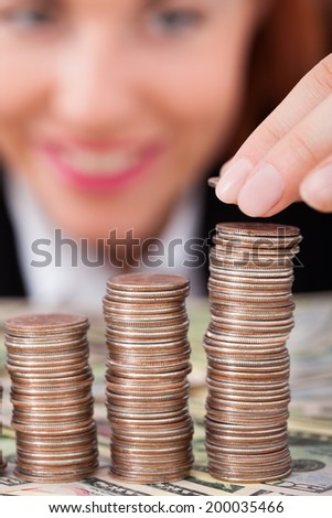 Cropped image of businesswoman stacking coins as bar graph at desk