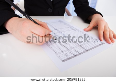 Cropped image of businesswoman writing on financial paper
