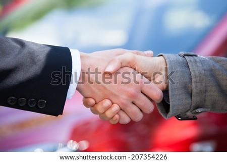 Cropped image of car dealer and female client shaking hands at dealership - stock photo