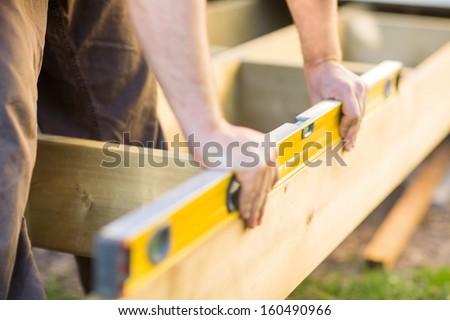 Cropped image of carpenter's hands checking level of wood at construction site - stock photo