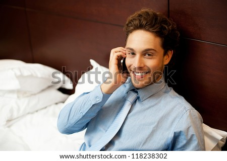 Cropped image of charming young man resting on headboard while talking on the phone - stock photo