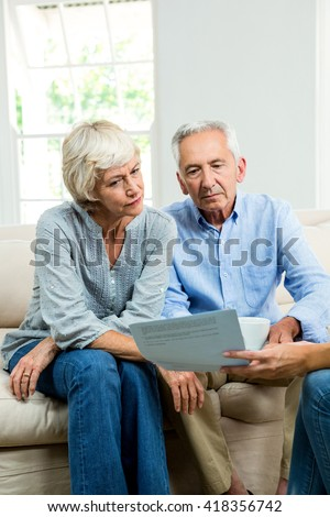 Cropped image of consultant showing report to senior couple at home - stock photo