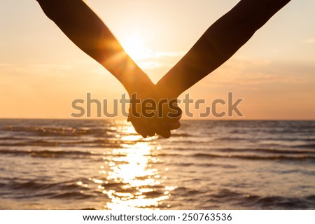 Cropped image of couple holding hands at beach during sunset