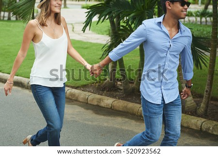 Cropped image of couple holding hands during walk in park