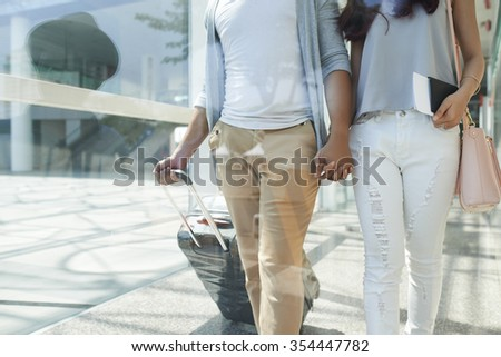 Cropped image of couple holding hands when walking through airport terminal - stock photo