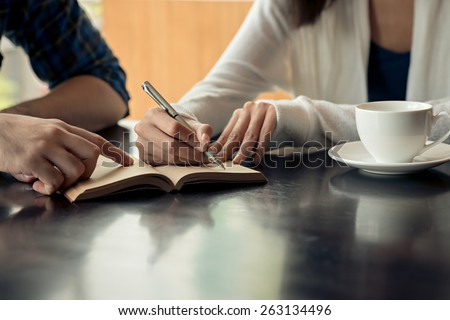 Cropped image of couple writing down business ideas