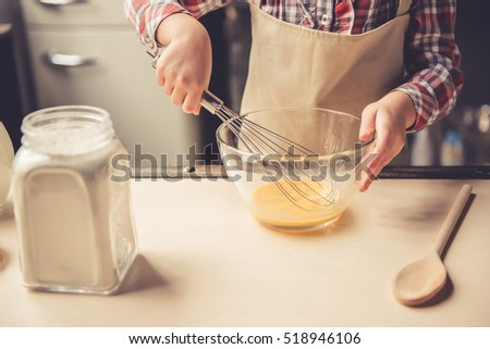 Cropped image of cute little girl whisking eggs in the bowl while preparing dough for baking