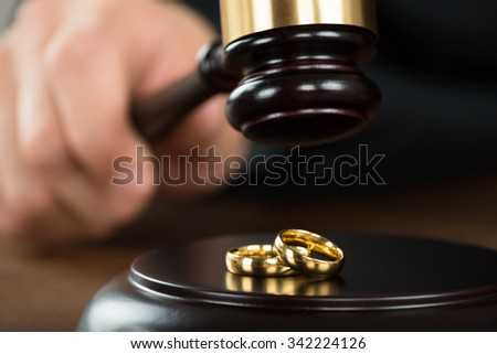 Cropped image of divorce judge hitting gavel on golden rings at desk in courtroom - stock photo