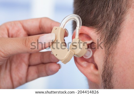 Cropped image of doctor inserting hearing aid in man's ear - stock photo