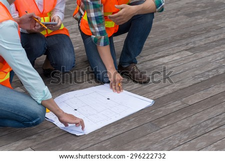 Cropped image of engineers discussing plan of the building - stock photo