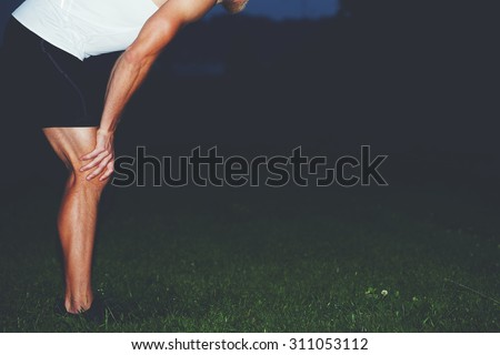 Cropped image of exhausted male jogger with muscular body taking break after run in the park while resting with hands on his knees against copy space area for your text message or advertising content - stock photo