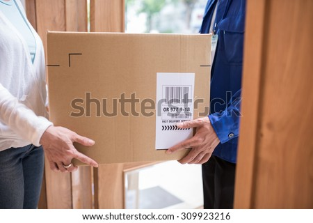 Cropped image of fast delivery service worker giving parcel to the client - stock photo