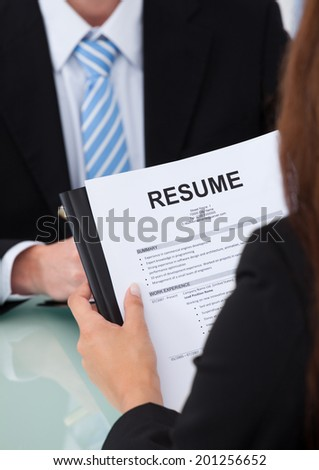 Cropped image of female candidate holding resume at desk during interview - stock photo