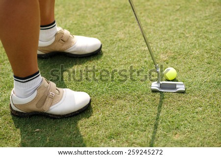 Cropped image of female golf player hitting ball with a putter