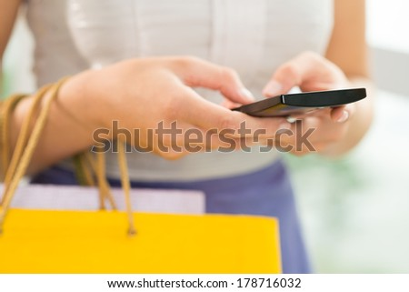 Cropped image of female hands carrying bags and dialing a telephone number on the foreground  - stock photo