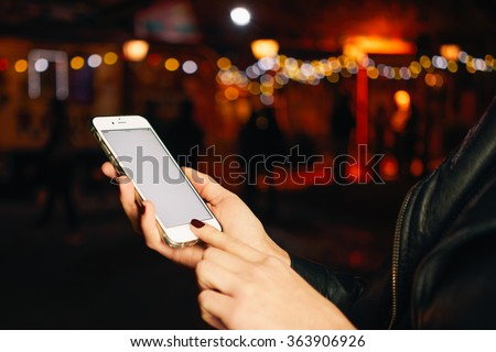 Cropped image of female hands holding mobile phone with blank copy space screen on a bokeh background - stock photo