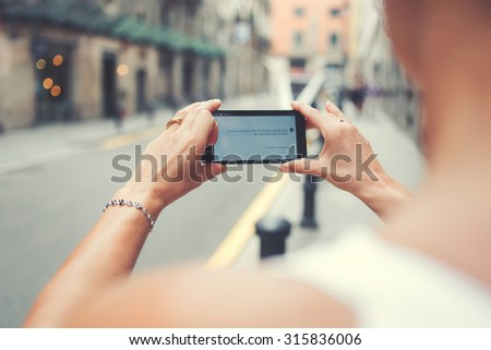 Cropped image of female photographing street view on her smart phone camera for chat message while strolling outside in the city, woman taking picture on cell telephone while walking around the city  - stock photo
