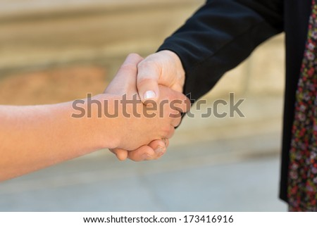 Cropped image of female university students shaking hands on campus