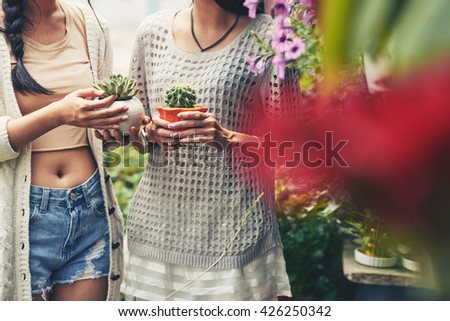 Cropped image of girl holding little cactuses - stock photo