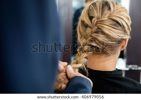 Cropped Image Of Hairdresser Braiding Client's Hair - stock photo