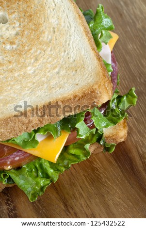 Cropped image of ham sandwich over a wooden background