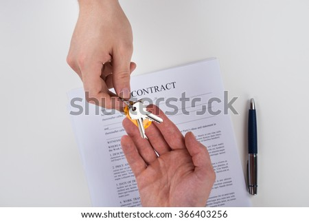 Cropped image of hand giving home keys to client with contract paper on desk - stock photo