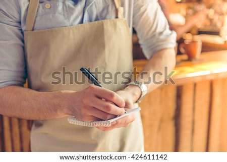 Cropped image of handsome young waiter making notes while taking an order, standing in the cafe - stock photo