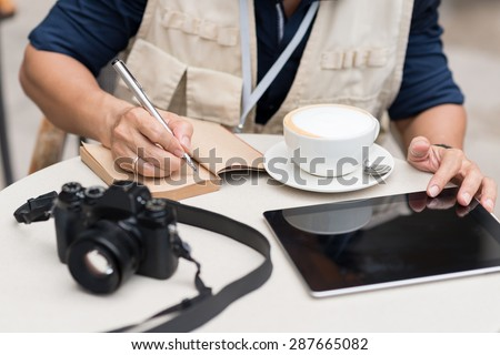 Cropped image of journalist making notes while sitting in the cafe - stock photo