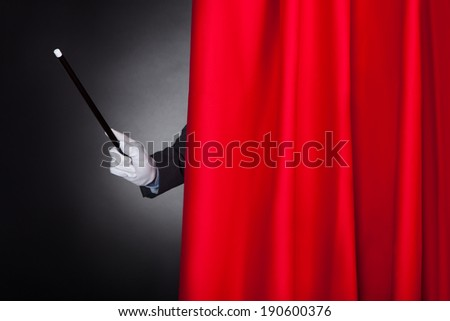 Cropped image of magician holding wand behind stage curtain - stock photo