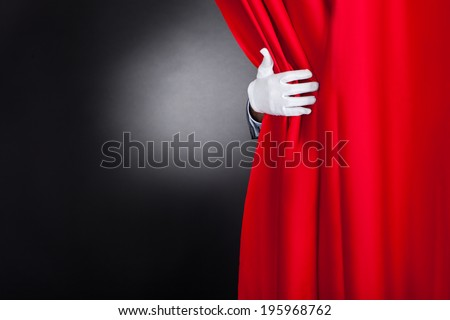 Cropped image of magician opening red stage curtain - stock photo