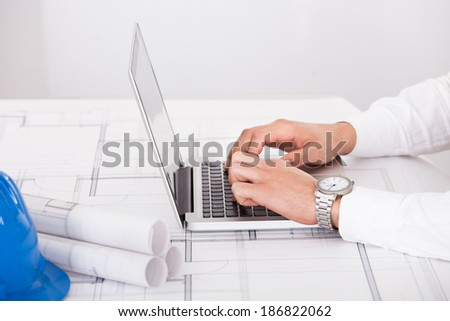 Cropped image of male architect using laptop in office - stock photo