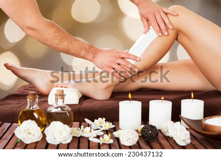 Cropped image of male beautician waxing woman's leg in spa - stock photo