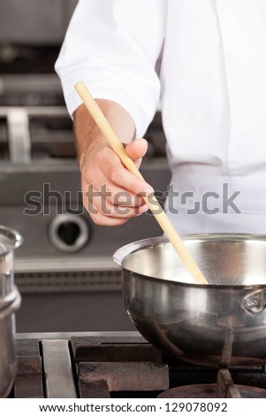 Cropped image of male chef preparing food in kitchen - stock photo